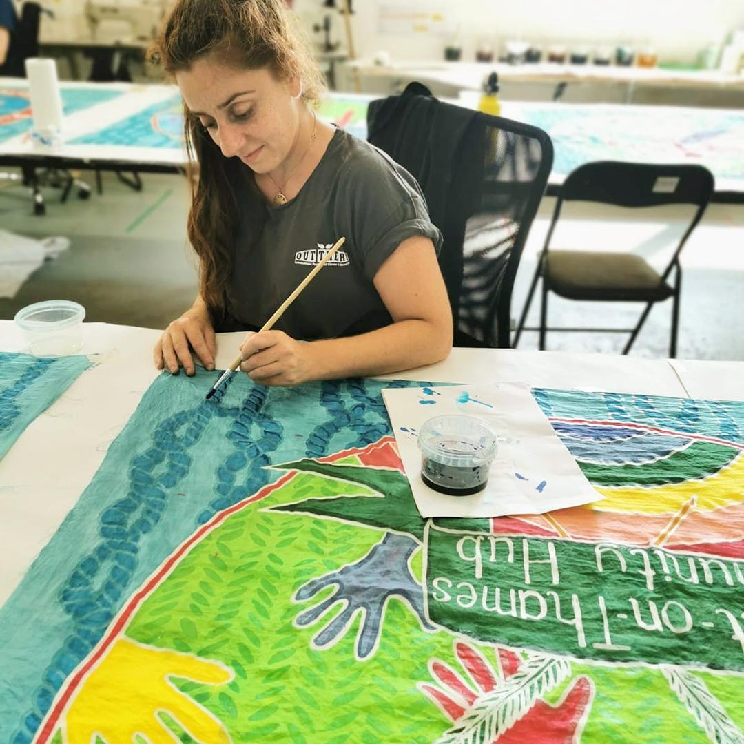 Taraneh Jahanpour painting the Community Hub flag