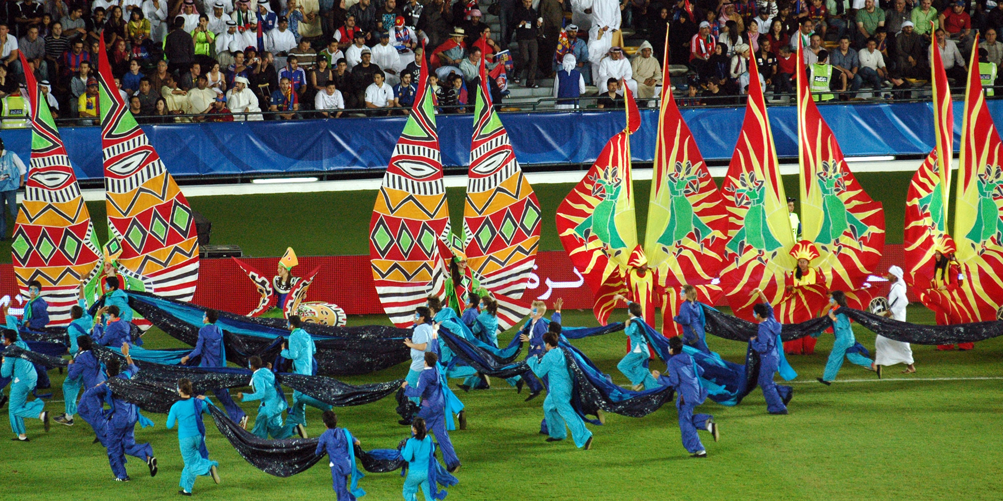 Large silk carnival costumes on a football pitch