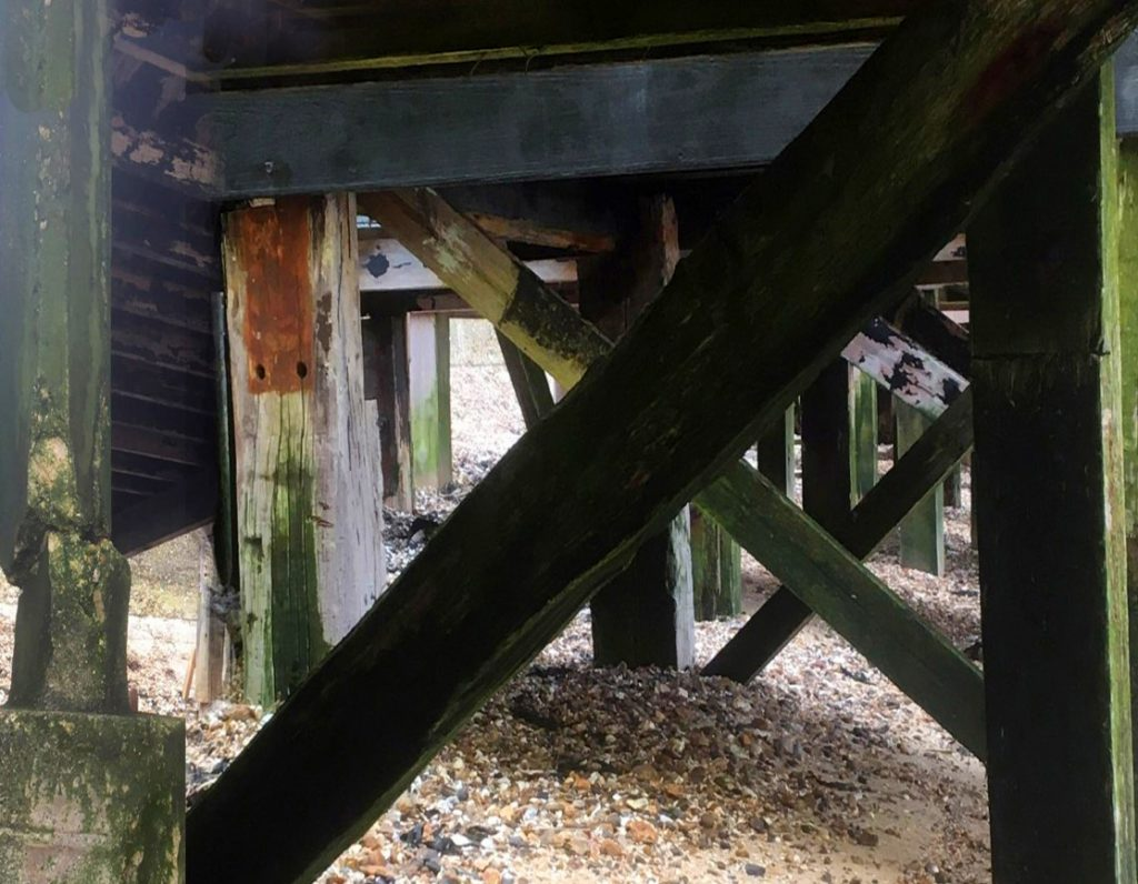 Wooden structures underneath beach huts