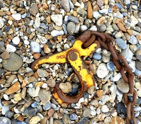 Mile 44 by Ali Fox: Rusted metal claw washed up on beach