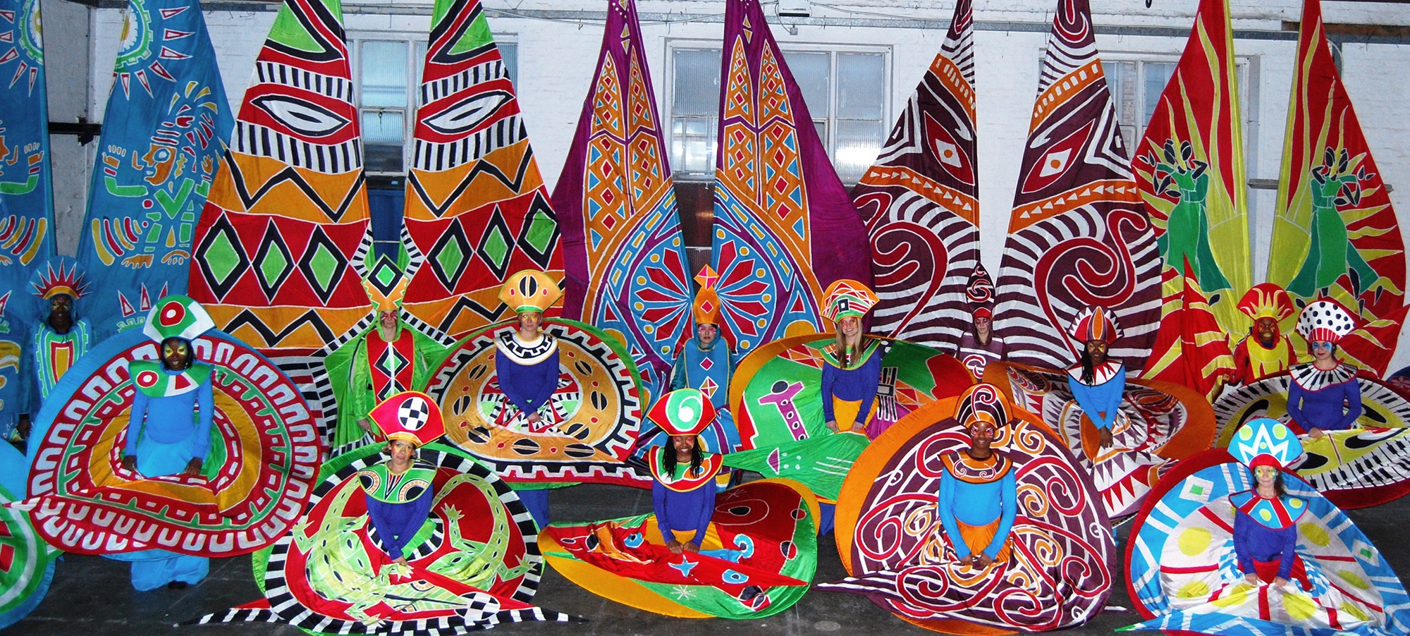 A group of people wearing large colourful silk carnival costumes