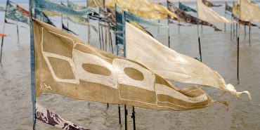 Flags on a beach, held by poles in the sand with the tide coming in